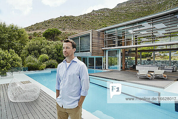 Mature man with hands in pockets looking away while standing against modern house