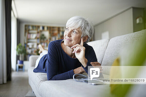 Contemplating senior woman looking away while lying on sofa at home