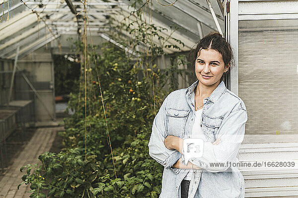 Confident young woman with arms crossed standing by greenhouse