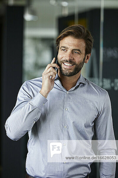 Businessman smiling while talking on mobile phone in office