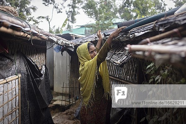 Rohingya woman covers the roof of her hut with a carpet to keep the interior dry during the heavy monsoon rains  Camp Kutupalong  Cox Bazaar  Bangladesh  Asia