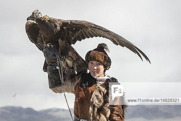 Young eagle hunter with her female eagle  Olgii  Mongolia  Asia