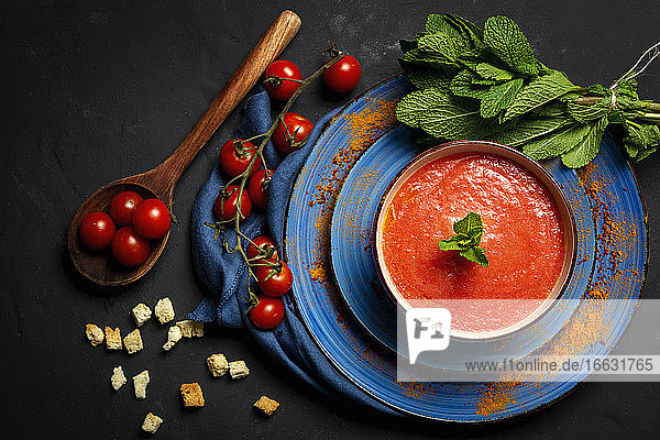 Healthy homemade tomato soup with bread  mint and olive oil on dark background