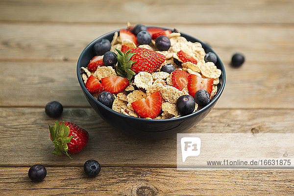 Breakfast bowl of corn flakes with strawberries and blueberries placed on wooden background