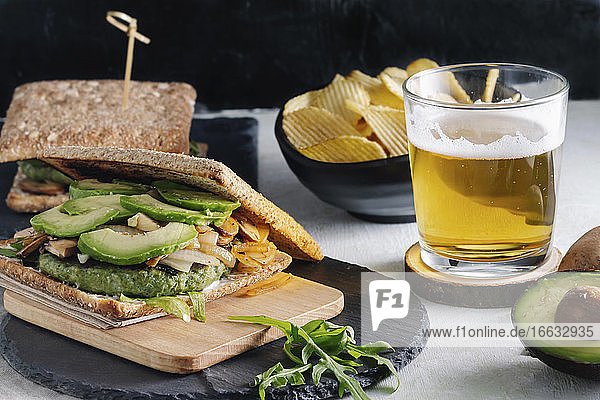 Tasty sandwich with avocado placed on table with glass of beer and potato chips in cafe