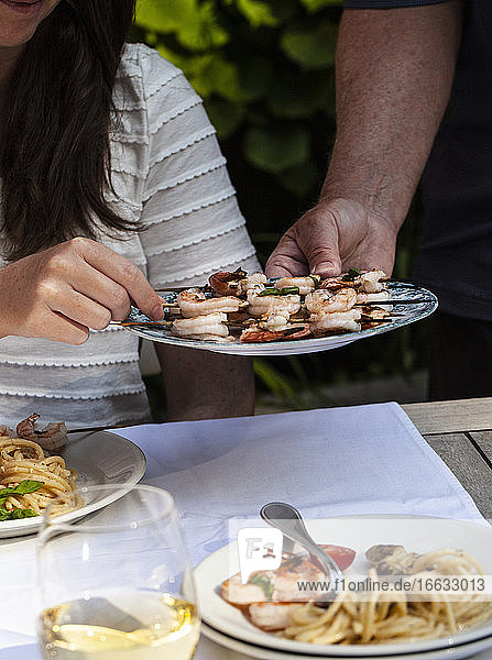 Platter of shrimp skewers being passed an an outdoor table with pasta and white wine