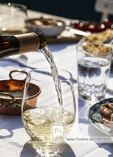 White wine being poured into a glass  on an outdoor table with pasta cacio e pepe (cheese and pepper)  basil and shrimp skewers