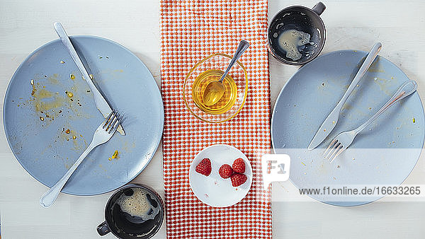 Top view of empty plates with forks and knifes and empty cups after delicious breakfast at home