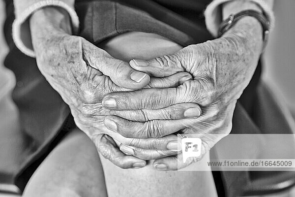 Elderly woman sitting with joined hands.