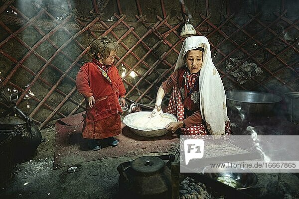 Woman and infant in traditional Kyrgyz traditional traditional traditional traditional traditional traditional traditional traditional traditional costume  dough production for flat bread  in front of her a teakettle on a fireplace  yurt  bozai gumbaz  wakhan corridor  Badakhshan  Afghanistan  Asia