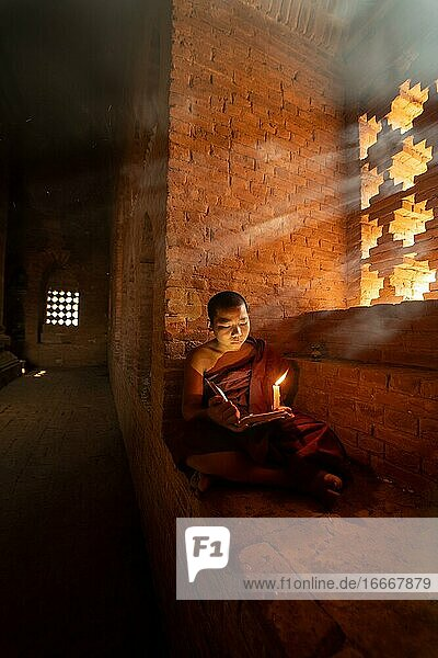 Buddhist young monk in red robe reading sitting in front of rays of light in a temple  Bagan  Myanmar  Asia