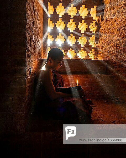 Buddhist young monk in red robe reading while sitting with a candle in front of rays of light in a temple  Bagan  Myanmar  Asia