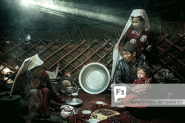 Two woman  a man and a child  morning meal  yurt  a ray of light falls in  nomadic Kyrgyz  Bozai Gumbaz  Wakhan corridor  Badakhshan  Afghanistan  Asia