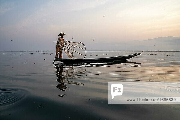 Traditional fisherman posing standing on his small boat in front of sunrise  Lake Inle  Myanmar  Asia