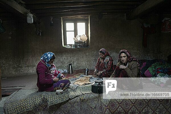 A woman with an infant and two other woman sitting on carpets in the living room of a traditional mud house  Khandud  Wakhan Corridor  Afghanistan  Asia