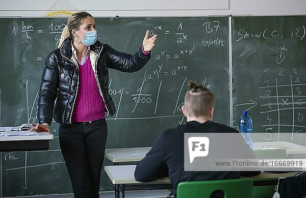 Teacher with winter jacket and face mask in classroom teaching  gestures  corona crisis  Stuttgart  Baden-Württemberg  Germany  Europe