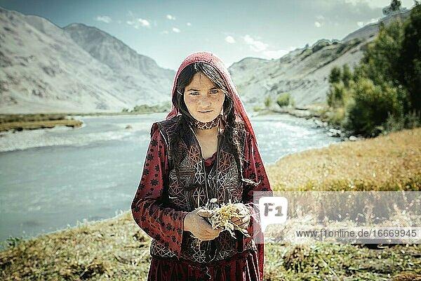 Girl  8 years  bundles small wheat yarbs  members of the ethnic group of the sedentary Wakhi  Khandud  Wakhan Corridor  Afghanistan  Asia