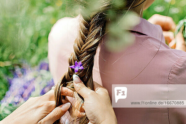 Girl braids a flower in a braid on nature
