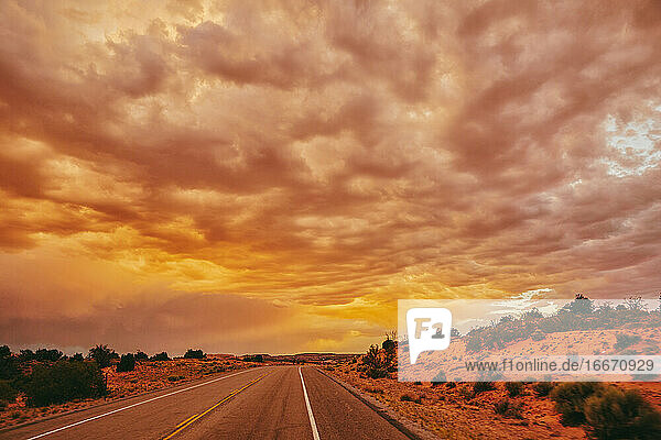 Golden sunset over storm clouds along empty highway in Moab  Utah.