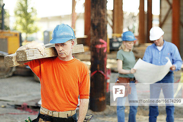 Portrait of male construction worker with two construction worke