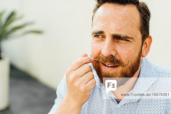 Bearded caucasian man with freckles touching his moustache