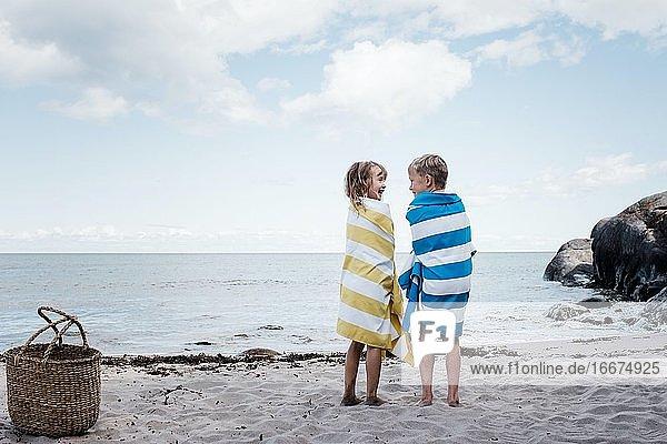 Bruder und Schwester standen lachend am Strand  in Handtücher gehüllt Bruder und Schwester standen lachend am Strand, in Handtücher gehüllt
