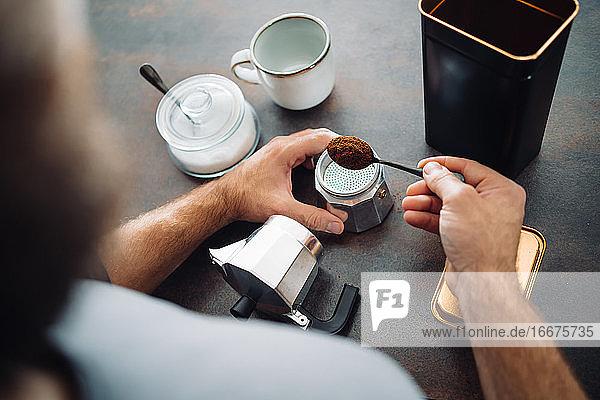 Unbekannter Mann füllt eine italienische Kaffeemaschine an der Küchenbar Unbekannter Mann füllt eine italienische Kaffeemaschine an der Küchenbar