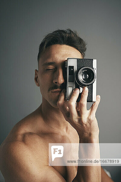 Retro de un chico moreno with bigote with analogical camara