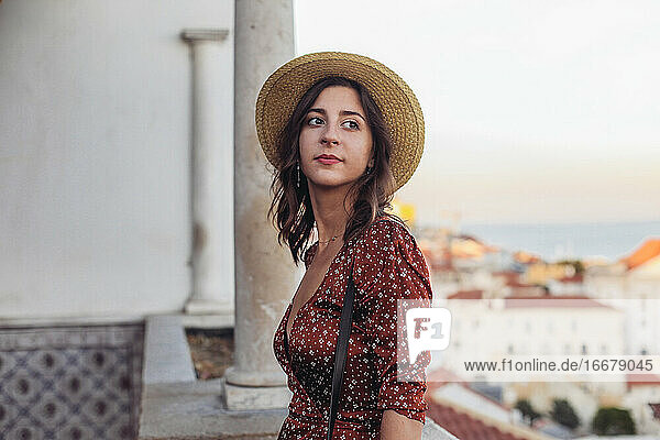 Woman in a straw hat looking aside and smiling  Lisbon sunset view
