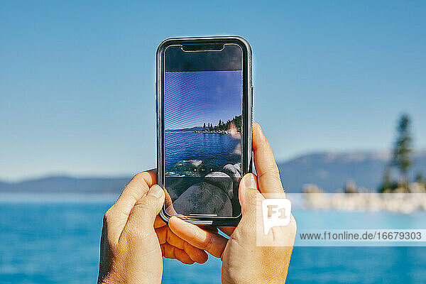 Young woman taking a picture of Lake Tahoe.