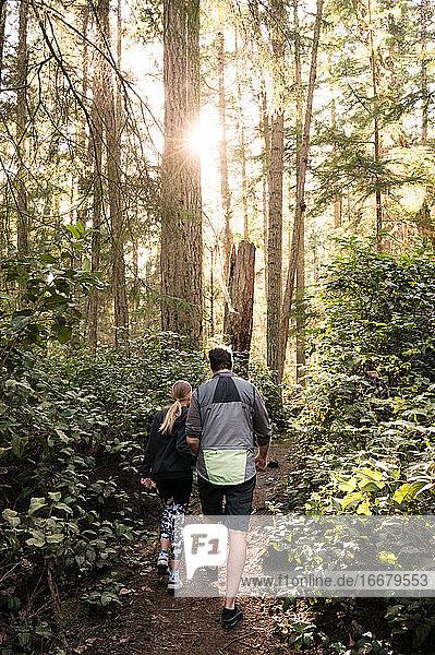 Vater und Tochter beim Wandern auf einem Waldweg an einem sonnigen Tag