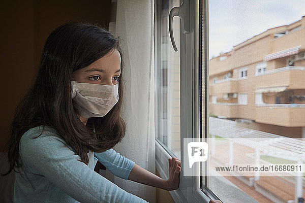 Girl with face mask looking out the window quarantined by covid-19