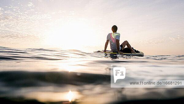 Konzept: Ruhe und Entspannung. Mann sitzt auf Paddel surfen Konzept: Ruhe und Entspannung. Mann sitzt auf Paddel surfen