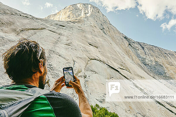 Young man taking picture of El Capitan Mountain in Yosemite Park.