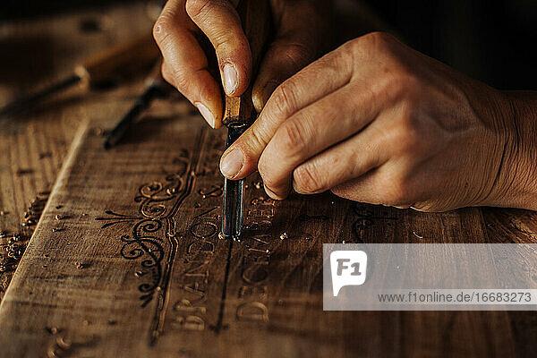 Nahaufnahme einer dekorativen Holzgravur mit Handwerkzeugen Nahaufnahme einer dekorativen Holzgravur mit Handwerkzeugen