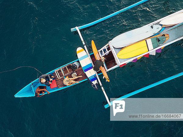 Luftaufnahme von Surfern und einem Boot auf dem Meer  Lombok  Indonesien Luftaufnahme von Surfern und einem Boot auf dem Meer, Lombok, Indonesien