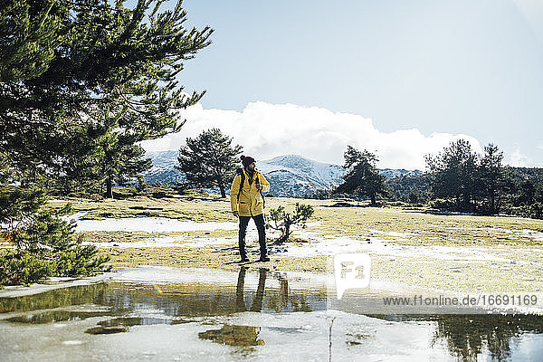 Young man with yellow jacket and backpack next to pond in the mountain