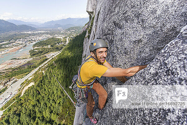 Man looking at camera while climbing multipitch on granite Squamish