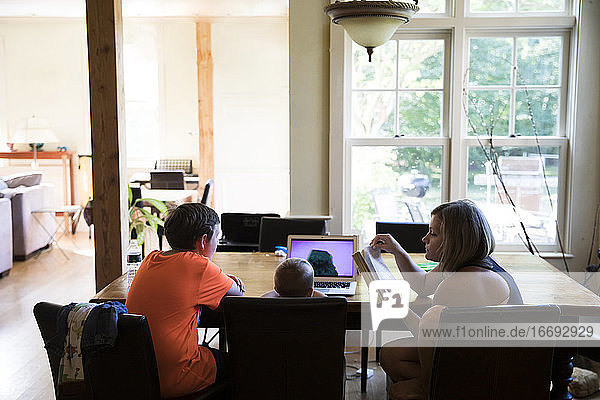 Mom and Toddler Son Watching Laptop Sit With Teenage Cousin at Table
