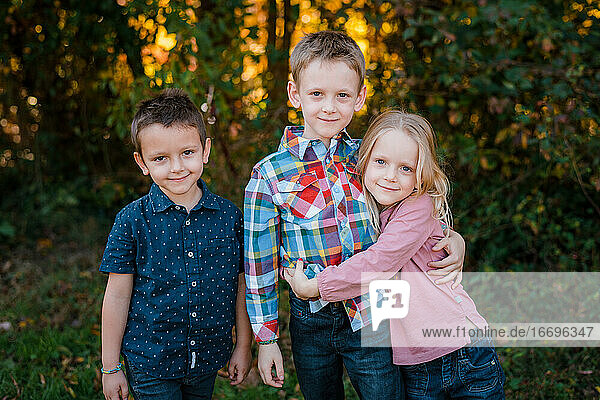 Family brothers and sister portrait outdoors in nature