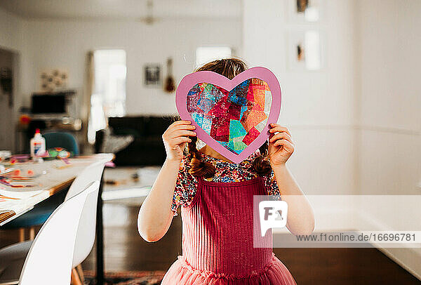 Young girl standing inside with rainbow heart in hands
