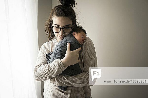 Hipster Millennial Mom Snuggles Swaddled Newborn Son Next to Window Hipster Millennial Mom Snuggles Swaddled Newborn Son Next to Window