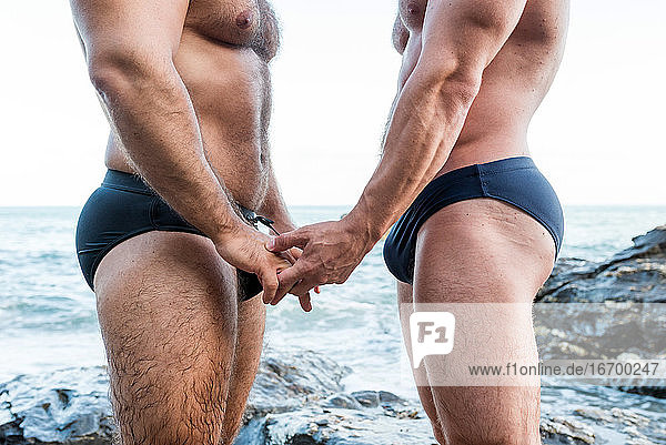 Lgbt pride concept. Muscled male gay couple holding hands detail. Seascape.