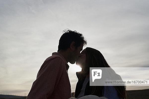 Schönes junges Paar  das sich bei Sonnenuntergang in einem Park küsst. Romantisches Konzept