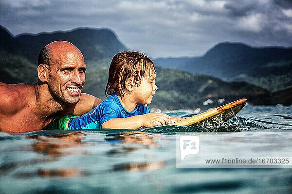 Vater und 3 Jahre alte Sonne paddeln auf einem hölzernen Surfbrett Vater und 3 Jahre alte Sonne paddeln auf einem hölzernen Surfbrett