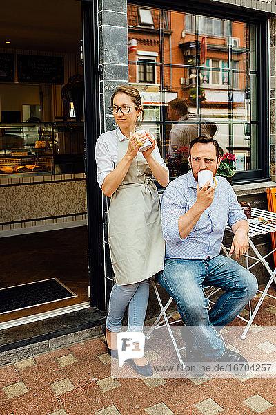 Mann und Frau  Cafébesitzerpaar beim Teetrinken am Eingang eines Cafés