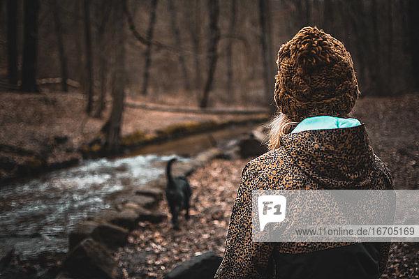 Mädchen mit Wolle  mit Hund  Hut sitzend am Fluss in einem Wald