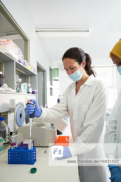 Female scientist in face mask using pipette at laboratory centrifuge