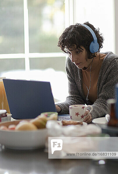 Woman with headphones working from home at laptop in kitchen