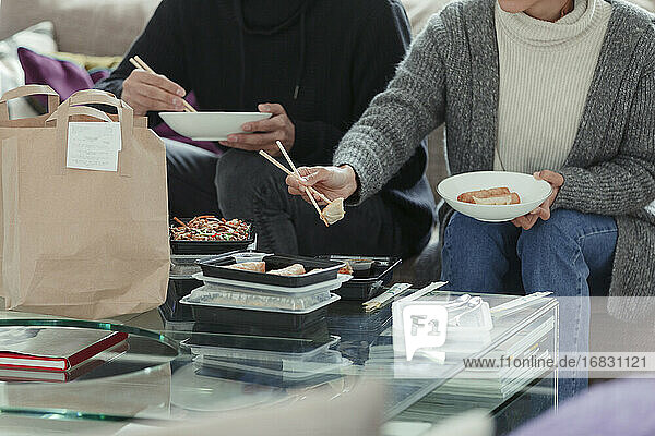 Couple enjoying takeout food with chopsticks in living room
